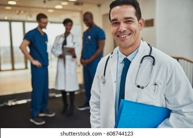 Successful handsome young Hispanic doctor with a beaming smile standing clutching a blue folder under his arm with his medical team in the background