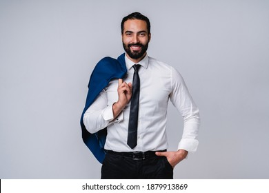 Successful handsome young Middle Eastern man in formal outfit isolated over grey background