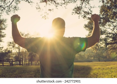 Successful happy accomplished man stands with raised arms facing the sun. White male athlete with arms up celebrating and happy with his achievement and exercise with a retro vintage filter.