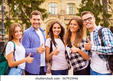 Successful happy best friends standing near campus and gesturing like.