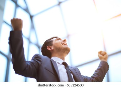 Successful happy businessman raises his arms up celebrating his victory
