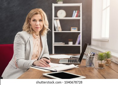 Successful happy businesswoman in formal wear sitting at wooden desk in modern office and working with report document, copy space