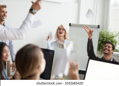 Successful happy diverse employee group launching paper planes together, excited young and old multiracial office workers having fun doing team building activity, teamwork synergy engagement concept