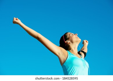 Successful happy fitness woman raising arms to the sky after sport achievement outdoor. Sporty girl enjoying freedom.