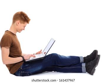 Successful happy man lying down o n floor using laptop