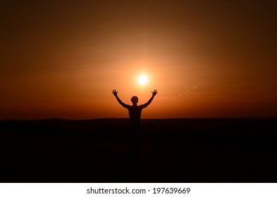 Successful happy man raising arms in summer at sunset.