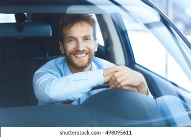 Successful and happy. Shot of a happy mature man smiling to the camera sitting in his brand new car at the local dealership