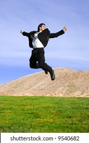 successful and happy young adult businessman running and jumping in the green field