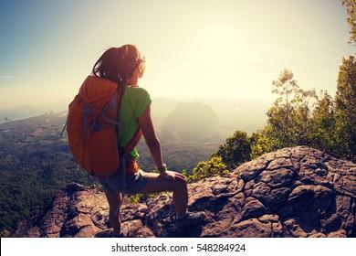 successful hiker hiking on sunrise mountain peak