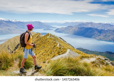 Successful hiker observing on mountain peak cliff edge. New Zealand