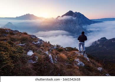 Successful hiker on top of mountain at sunrise