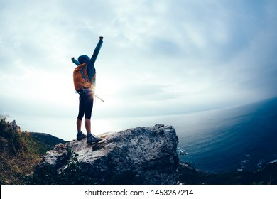 Successful hiker outstretched arms at seaside mountain top cliff edge