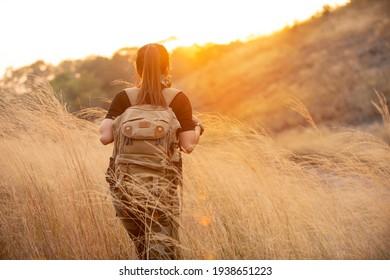 Successful hiker woman walking a mountain path looking sunset on meadow mountain.