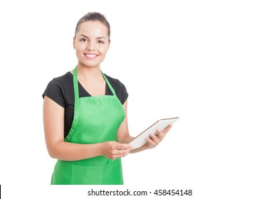 Successful hypermarket employee with green apron holding modern tablet isolated on white background with copyspace