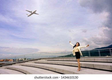 Successful Independent Business Woman standing on the top of open space open her arms up to the air with airplane flying in the sky as background