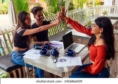 Successful indian businesswoman and businessman at work surfing online freelancer freelance in summer tropical cafe.three friends communicating with tea each other meeting