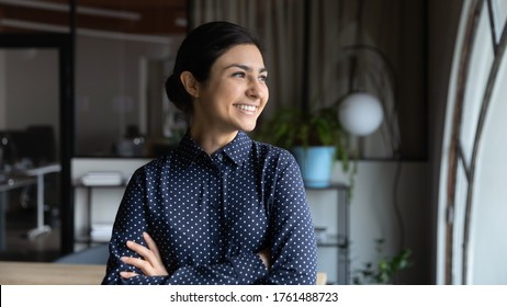 Successful Indian businesswoman, promoted employee headshot. Confident lady boss with arms crossed standing in modern office looking out the window feels proud by achievement, business goes up concept
