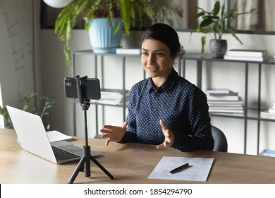 Successful Indian businesswoman recording webinar, using smartphone on tripod, sitting at desk in office, smiling young employee business coach teacher influencer shooting video for blog, speaking