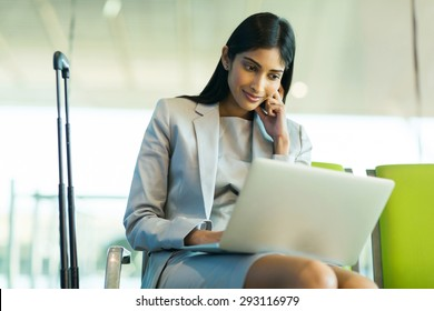 successful indian businesswoman using laptop computer at airport