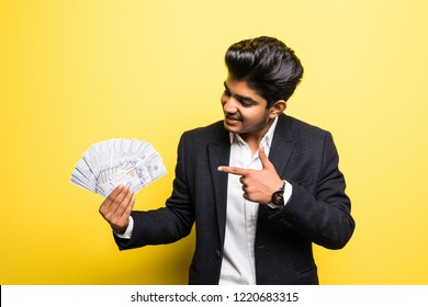 Successful Indian entrepreneur wearing with dollar banknotes in hand classical suit looking at camera with toothy smile while standing against yellow background