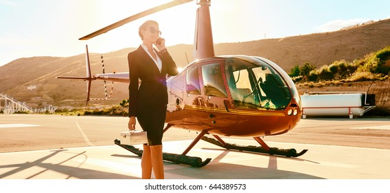 Successful intelligent smart elegant young businesswoman talk by phone near helicopter, mountains sunny day. Woman in business, ceo director female, success, career, good deal luxury lifestyle concept