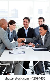 Successful international business people shaking hands in the office