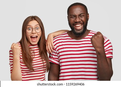 Successful interracial female and male friends students clench fists with triumph, have overjoyed facial expressions, rejoice succssfully passed exam, stand next to each other against white wall
