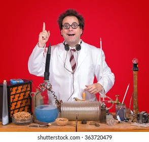 successful inventor at his desk with equipment on red background. Genius professor shows triumph for invention. Successful scientific research. The inventor of celebrating success in the lab.