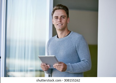 Successful investment banker busy looking up the exchange rates on his tablet in the morning looks over and smiles at the camera