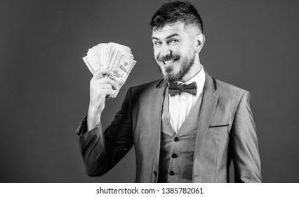A successful investment. Currency broker with bundle of money. Making money with his own business. Bearded man holding cash money. Rich businessman with us dollars banknotes. Business startup loan.