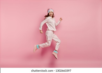 Successful joyful female feels like winner, jumps high in air, wears casual pyjamas and eyemask, wakes up in high spirit, isolated over pink background. People, rest, emotions and sleeping concept