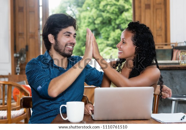 Successful latin american couple give high five indoor at home