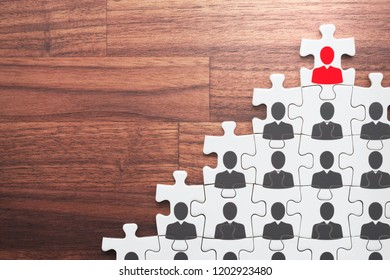 Successful leader and corporate hierarchy. Human resource management and leadership concept. Assembling jigsaw puzzle on wood desk.