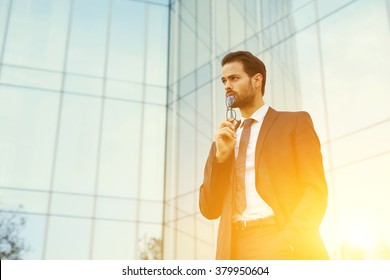 Successful luxury businessman put glasses to his lips and looking on copy space while standing outdoors, skilled male entrepreneur thinking about something serious after meeting with important clients