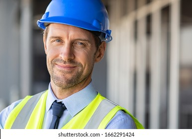 Successful male architect at building site looking at camera. Confident construction manager wearing blue helmet and yellow safety vest with copy space. Portrait of successful mature civil engineer.