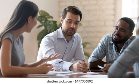 Successful male corporate leader explain new project plan talk to diverse team people training staff at meeting, serious boss teach multiracial workers discuss paperwork at group office briefing