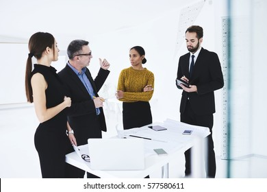 Successful male executive of company analyzing work of financial department giving advice how to improve achievements during council with employees in coworking space using modern devices and wifi