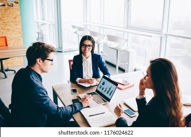 Successful male and female economists discussing ideas for good trade using finance graphic on modern laptop computer for analyzing, confident colleagues making business conference in meeting room