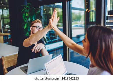Successful male and female freelancers high five to each other and feeling good from well done work with it project, partners enjoying cooperation sitting at table with netbook with mock up screen