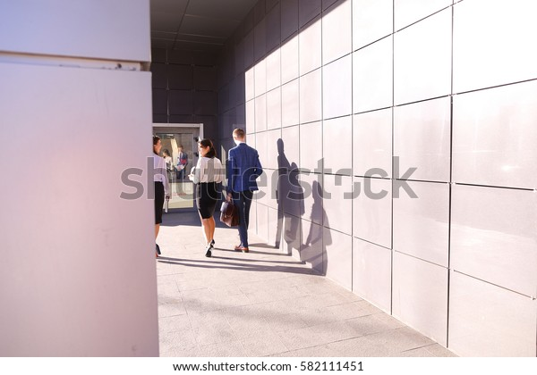 Successful male guy, businessman and two pretty young women, business people, students go in opposite direction from camera and discuss working day, returning from lunch break, study plans and kept