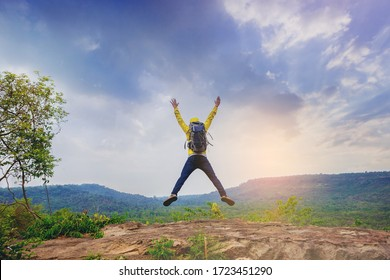 Successful male hiker jumping on mountain peak celebrate his freedom