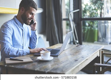 Successful male owner of business company talking with operator while making banking online consulting about cash remittance paying for bills using wireless internet and modern laptop in cabinet