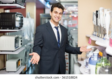Successful male seller at household appliances section of supermarket