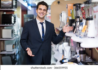 Successful male seller at household appliances section of a supermarket