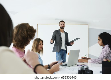 Successful male speaker talking with international students about business management during productive training in stylish college interior,portrait of talented coach during workshop indoors