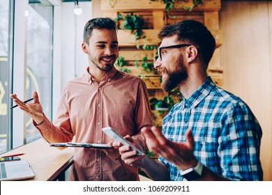 Successful male startuppers discussing plan together for work smiling and gesturing, happy hipster guys having friendly conversation about business information having meeting in coworking office