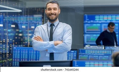 Successful Male Stock Trader Crosses Arms and Smiles at the Camera. In the Background Busy Stock Exchange Office with Traders, Brokers and Dealers Selling and Buying Bonds. Displays Show Numbers.
