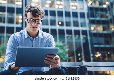 Successful male trader in trendy formal wear reading financial news on internet websites using 4G internet on modern tablet sitting outdoors on street of business city with modern skyscrapers