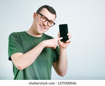 successful man advertises phone, studio photo over background