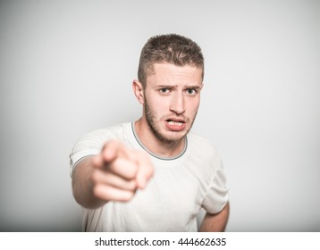 successful man angry points a finger at you, isolated on a gray background